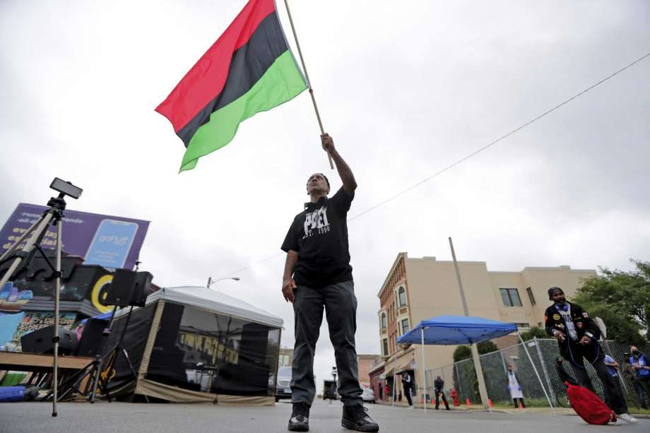 Duncan Ellington waves an African flag during a protest rally for Jacob Blake near Martin Luther King Park on West Vliet Street in Milwaukee, Saturday, Sept. 12, 2020. Blake was shot by police on Aug. 23 as he was being arrested in Kenosha, Wis. (Mike De Sisti/Milwaukee Journal-Sentinel via AP) Photo: Mike De Sisti, AP / Milwaukee Journal Sentinel