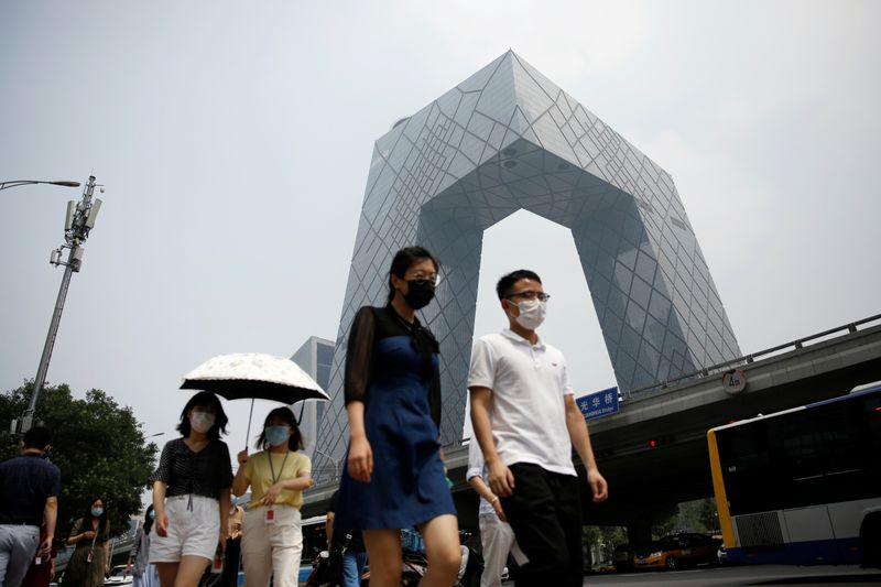 © Reuters. People wearing face masks walk past the CCTV headquarters in Beijing