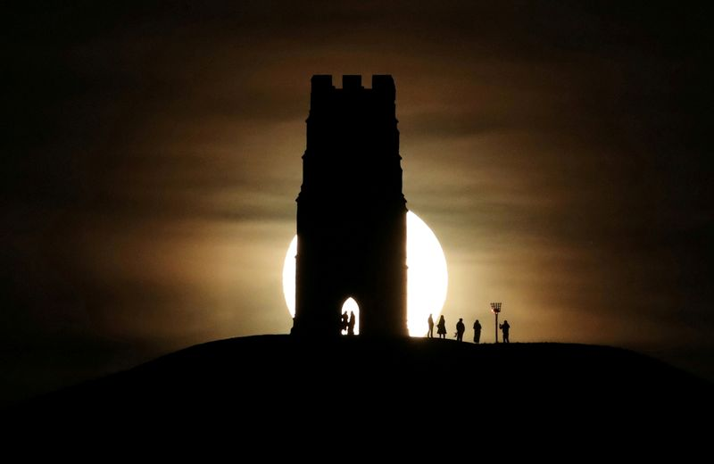 © Reuters. FILE PHOTO: St Michael's Tower is seen on Glastonbury Tor as a full moon rises in Glastonbury
