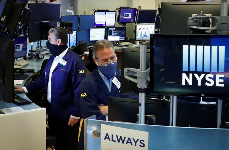 © Reuters. Traders wearing masks work, on the first day of in person trading since the closure during the outbreak of the coronavirus disease (COVID-19) on the floor at the NYSE in New York
