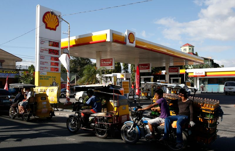 © Reuters. FILE PHOTO: Residents transport commuters and soda bottles on tricycles past a Shell petrol station in Las Pinas