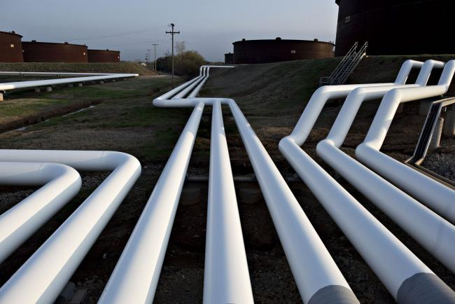 © Bloomberg. Pipelines run near oil storage tanks in Cushing, Oklahoma. Photographer: Daniel Acker/Bloomberg
