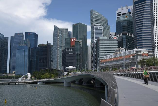 "© Bloomberg. A cyclist rides on Esplanade bridge as buildings stand in the Central Business District in Singapore on Monday, July 6, 2020. Prime Minister Lee Hsien Loong vowed to hand over Singapore ""intact"" and in ""good working order"" to the next generation of leaders, predicting the coronavirus crisis will ""weigh heavily"" on the nation's economy for at least a year. Photographer: Wei Leng Tay/Bloomberg"