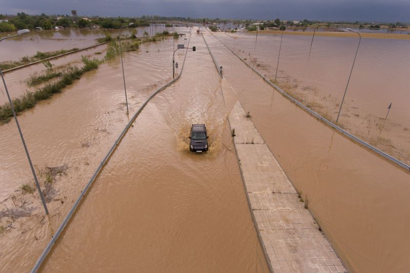 © Reuters. A car is seen on a flooded highway following a storm near the village of Artesiano