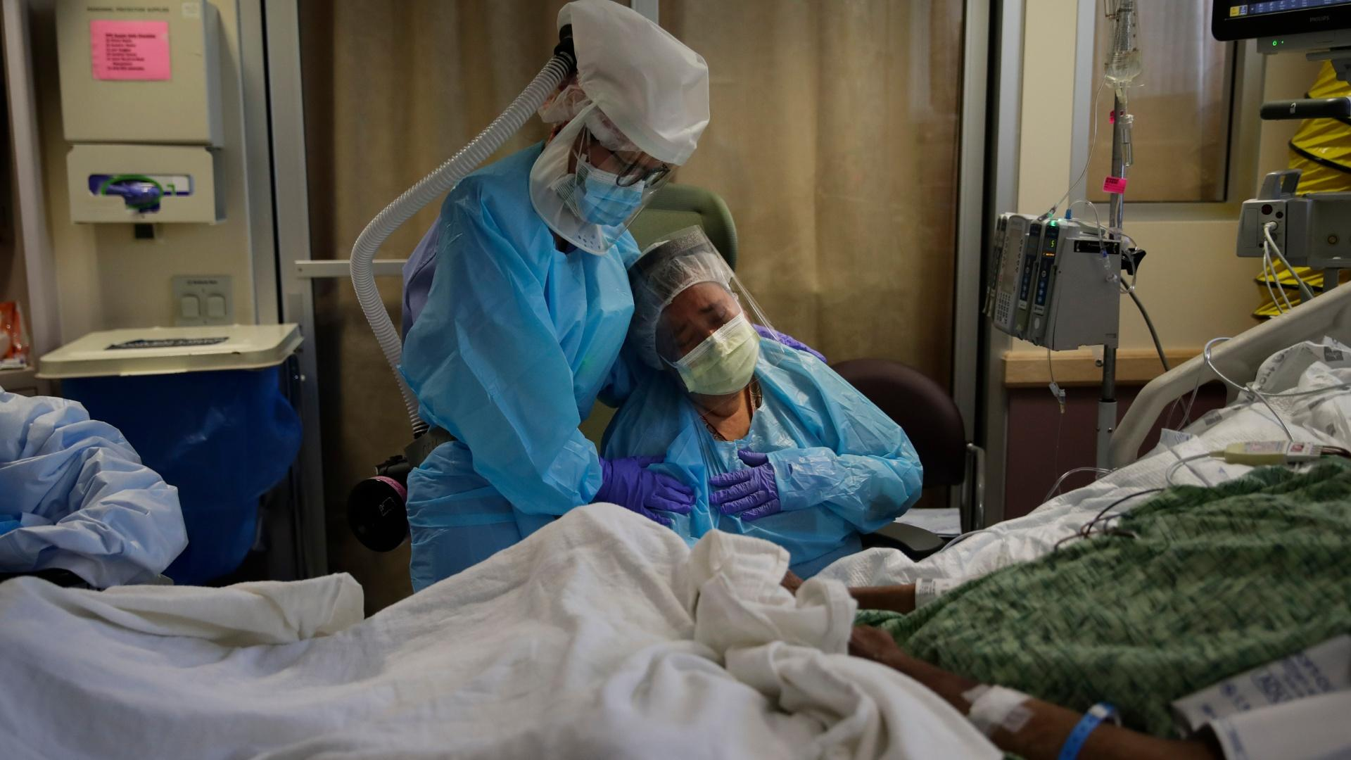In this July 31, 2020, file photo, Romelia Navarro, right, is comforted by nurse Michele Younkin as she weeps while sitting at the bedside of her dying husband, Antonio, in St. Jude Medical Center's COVID-19 unit in Fullerton, Calif. (AP Photo / Jae C. Hong, File)