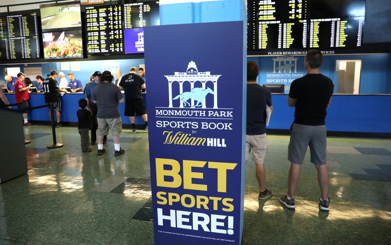 © Reuters. FILE PHOTO: Gamblers place bets on sports at Monmouth Park Sports Book by William Hill, shortly after the opening of the first day of legal betting on sports in Oceanport