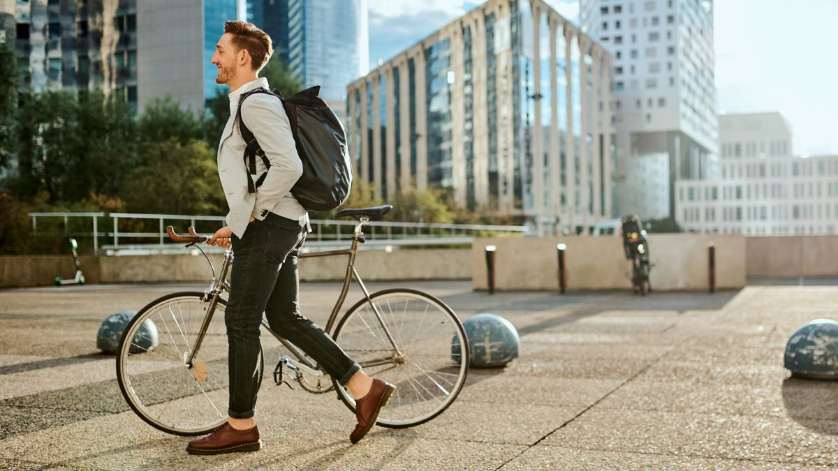 Man walking with bike on commute to work