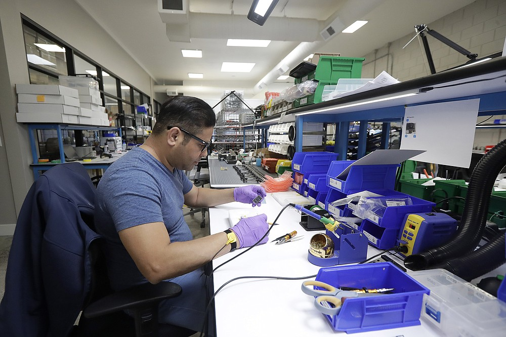 In this June 22, 2018, photo, Skydio tech assembler Alex Nakmoto works on the R1 flying camera drones in a laboratory in Redwood City, Calif. Skateboarders, surfers and YouTube stars used to be the target customers for California drone startup Skydio, which builds sophisticated self-flying machines that can follow people around and capture their best moves on video. Now it's police officers and soldiers getting equipped with the pricey drones. U.S. political and security concerns about the world's dominant consumer drone-maker, China-based DJI, have opened the door for Skydio and other companies to pitch their drones for government and business customers. (AP Photo/Jeff Chiu)
