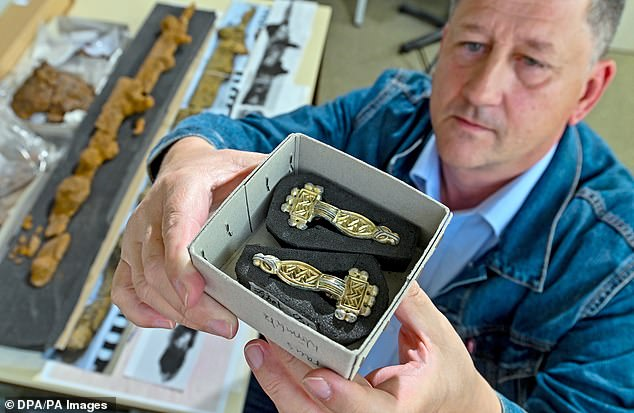 Archaeologist Arnold Muhl shows artistic vestment clasps in his workshop. The objects are 1,500 years old and come from 60 undamaged graves alongside the tomb of a Germanic lord who lived during the Great Migration