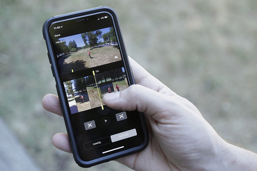 In this June 22, 2018, photo, Skydio head of marketing Patrick Stahl holds his phone showing videography intern Henry Belcaster on the screen as they demonstrate using an R1 flying camera drone in Redwood City, Calif. Skateboarders, surfers and YouTube stars used to be the target customers for California drone startup Skydio, which builds sophisticated self-flying machines that can follow people around and capture their best moves on video. Now it's police officers and soldiers getting equipped with the pricey drones. U.S. political and security concerns about the world's dominant consumer drone-maker, China-based DJI, have opened the door for Skydio and other companies to pitch their drones for government and business customers. (AP Photo/Jeff Chiu)