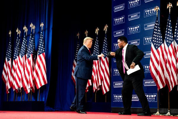 President Donald Trump fist bumps Herschel Walker, a former professional football player, as he arrives at the Cobb Galleria in Atlanta to deliver remarks on Black Economic Empowerment.