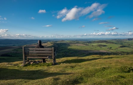 A hiker sits on a bench looking out over the mid-Wales countryside from Corndon Hill