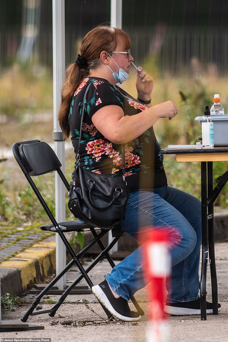 A woman is pictured taking a swab test for coronavirus at a centre in Bolton this morning. Other people in the town say they are struggling to get appointments for tests