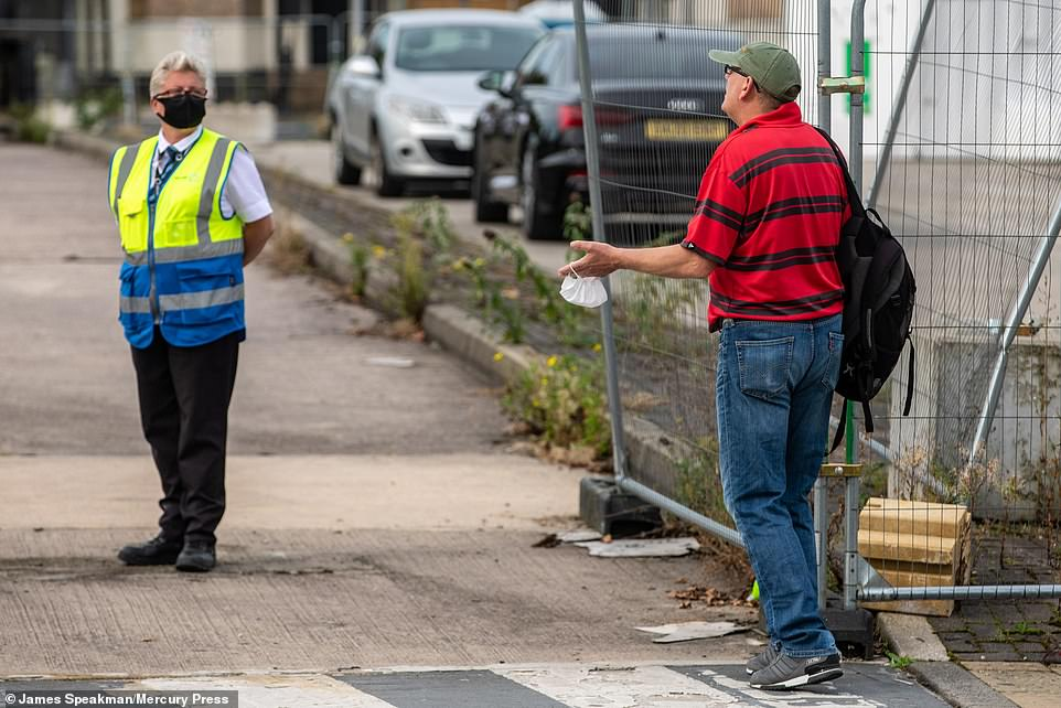 Another man denied entry to the testing site in Bolton pleads his case with a member of staff