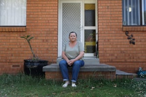 Angela Cadwallen sits outside her home