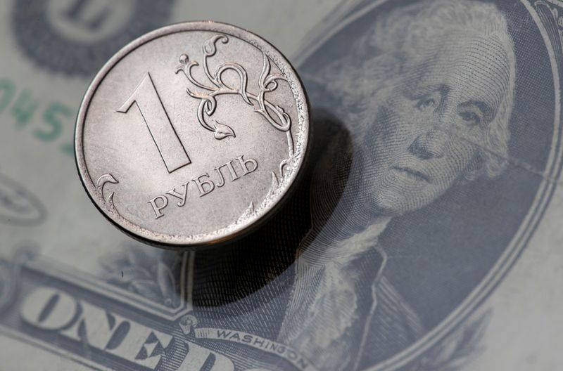 © Reuters. FILE PHOTO:  A view shows a Russian rouble coin and a U.S. dollar banknote in this picture illustration