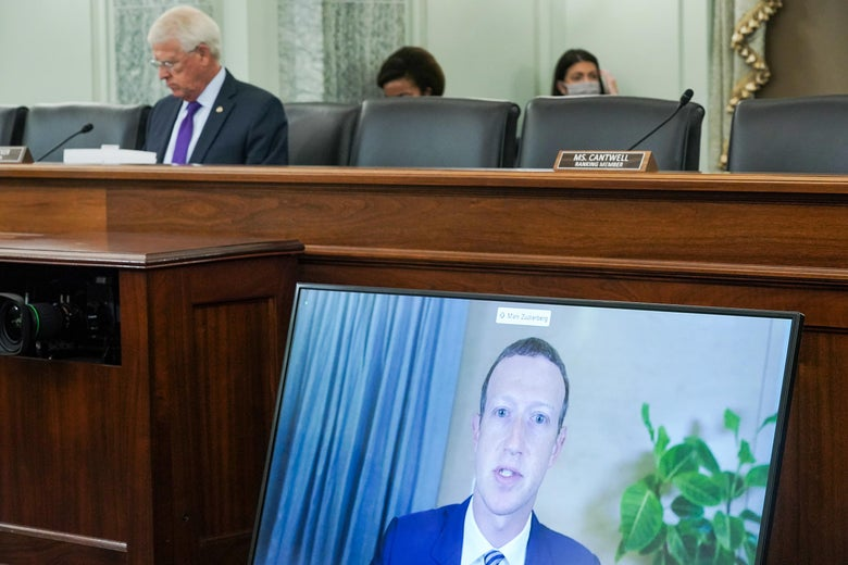 Mark Zuckerberg is on a large screen propped up against the desk where one senator sits.