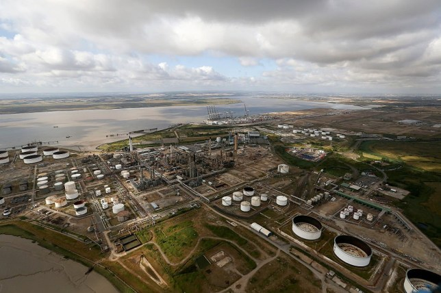 The Coryton oil refinery sits inactive as shipping cranes stand on the shoreline beyond at DP World Ltd.'s London Gateway deep-sea port, in this aerial photograph taken over Stanford-le-Hope, U.K., on Wednesday, July 22, 2015. U.K. economic growth accelerated in the second quarter as business services and finance strengthened and North Sea output surged. Photographer: Chris Ratcliffe/Bloomberg via Getty Images