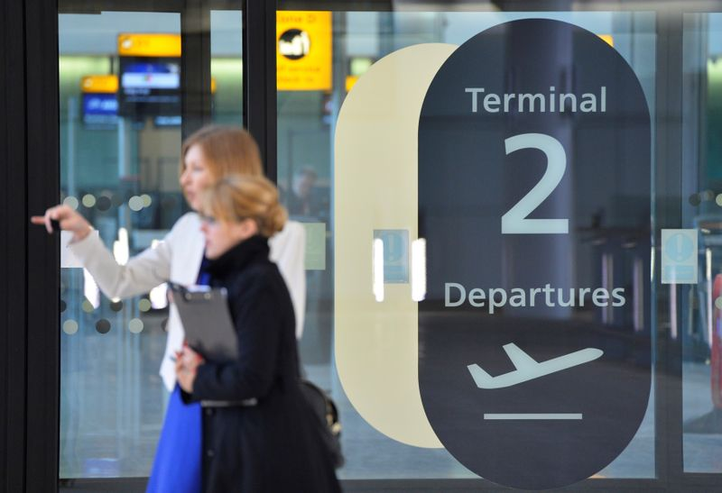 © Reuters. FILE PHOTO: Visitors are seen in a doorway at the departure area of the new 'Terminal 2: The Queen's Terminal' during a media event in Heathrow Airport, west London