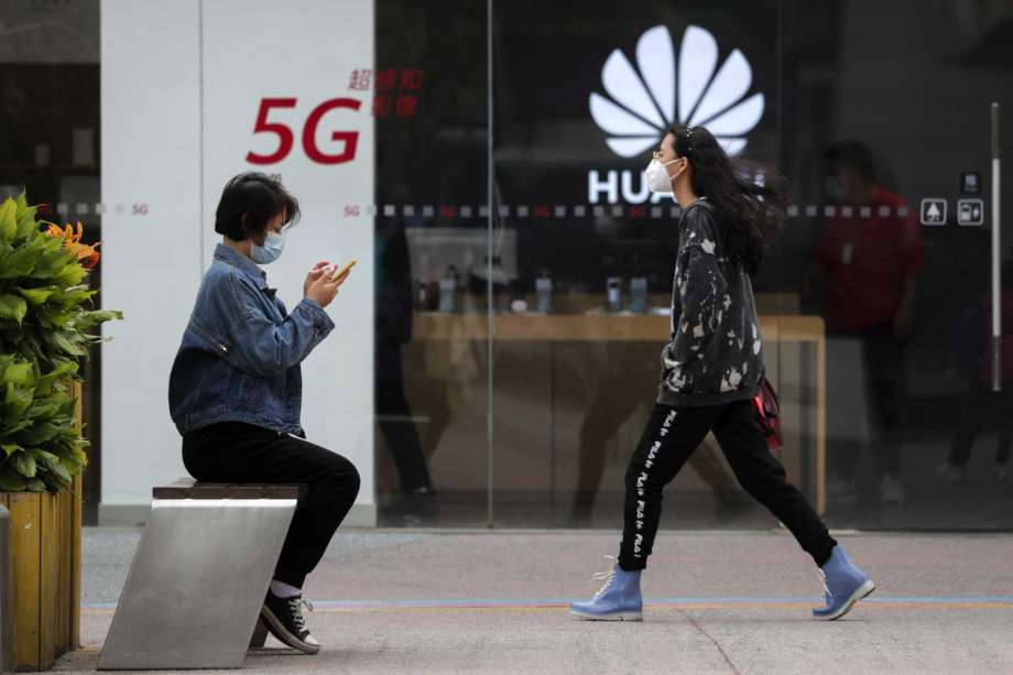 A woman wearing a face mask to help curb the spread of the coronavirus browses her smartphone as a masked woman walks by the Huawei retail shop promoting it 5G network in Beijing on Oct. 11, 2020. Chinese leaders are meeting to formulate an economic blueprint for the next five years that is expected to emphasize development of semiconductors and other technology amid a feud with Washington that is cutting off access to U.S. components for China's fledgling tech industries. Photo: Andy Wong, AP / Copyright 2020 The Associated Press. All rights reserved