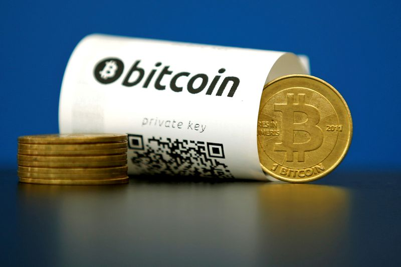 © Reuters. FILE PHOTO: An illustration photo shows a Bitcoin (virtual currency) paper wallet with QR codes and a coin are seen at La Maison du Bitcoin in Paris