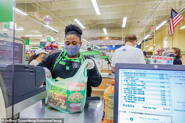 At one grocery store in Boston in May, one in five workers tested positive, indicating a 20% infection rate, which is 15 to 22 times higher than the general population rate of 0.9% to 1.3% at that time. Pictured: A Publix cashier bags groceries in Miami Beach, Florida, May 2020