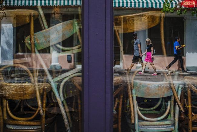© Bloomberg. Pedestrians are reflected in the windows of a closed restaurant in the South Beach neighborhood of Miami Beach, Florida, U.S., on Friday, March 20, 2020. Mayor Carlos Gimenez announced Wednesday that all public beaches, non-essential retail, private educational facilities, casinos and entertainment activities in Miami-Dade County will close as of Thursday night. Photographer: Scott McIntyre/Bloomberg