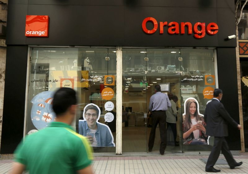 © Reuters. FILE PHOTO: People walk past a shop of French telecom operator Orange in Cairo