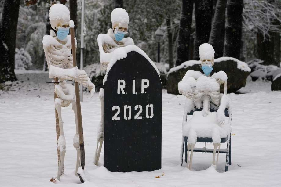 Snow falls on masked skeletons ready to bury the year 2020, Friday, Oct. 30, 2020, on a lawn in North Andover, Mass. Photo: Elise Amendola, AP / Copyright 2020 The Associated Press. All rights reserved.