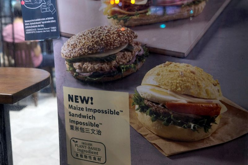 © Reuters. FILE PHOTO: A poster showing product from plant-based burger maker Impossible foods been using at Starbucks, in Hong Kong