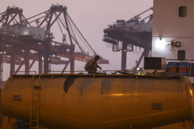 © Bloomberg. A driver checks a cement tanker truck at the Jawaharlal Nehru Port, operated by Jawaharlal Nehru Port Trust (JNPT), in Navi Mumbai, Maharashtra, India, on Saturday, Dec. 16, 2017. Many of the cargo containers passing through India's busiest port in Mumbai have a small piece of Japan Inc. attached: Devices from NEC Corp. that can be tracked as the containers rumble through the interior of Asia's third-largest economy. Photographer: Dhiraj Singh/Bloomberg
