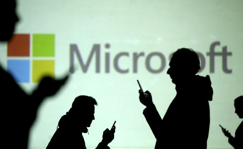 © Reuters. FILE PHOTO: FILE PHOTO: FILE PHOTO: Silhouettes of mobile users are seen next to a screen projection of Microsoft logo in this picture illustration