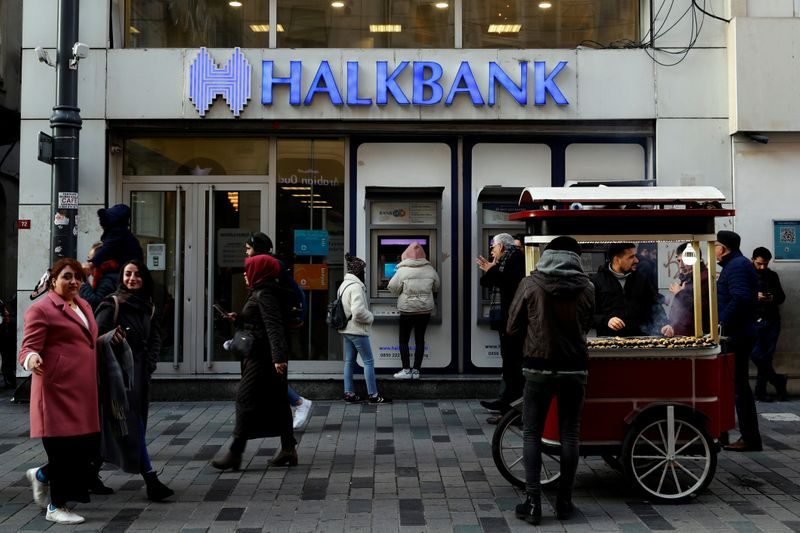 © Reuters. FILE PHOTO: People walk past by a branch of Halkbank in central Istanbul