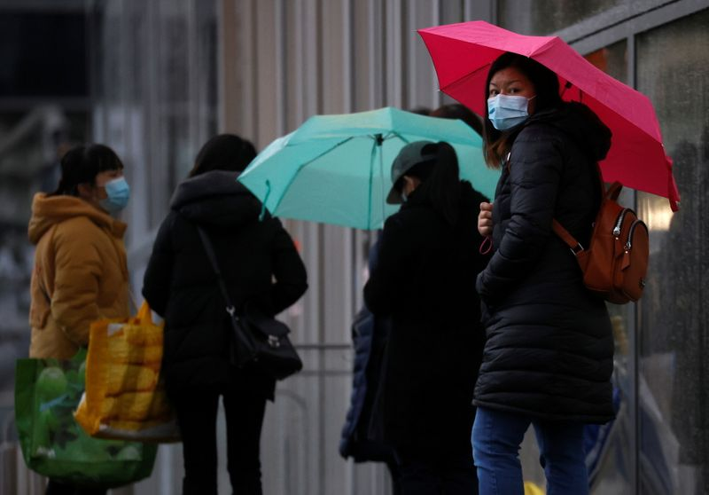 © Reuters. People wearing face masks shelter under umbrellas outside a department store following the outbreak of the coronavirus disease (COVID-19) in Manchester Briain