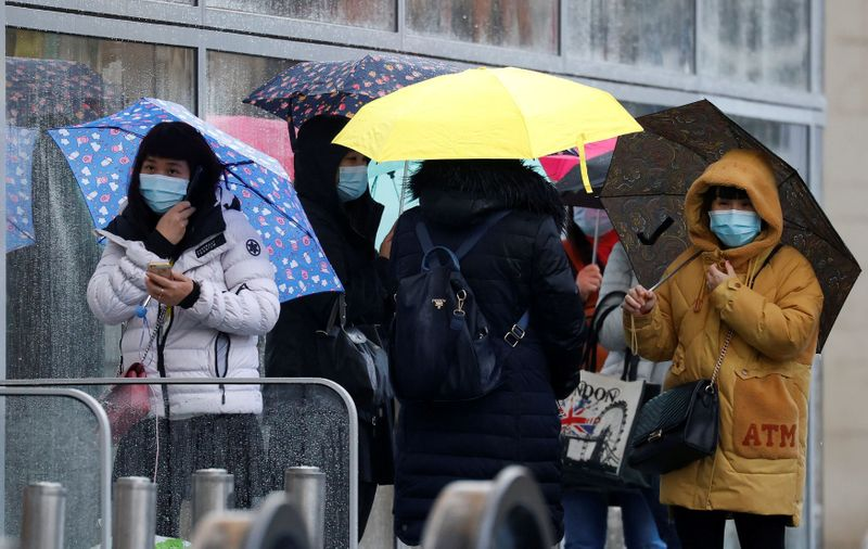 © Reuters. FILE PHOTO: People wearing face masks shelter under umbrellas outside a department store following the outbreak of the coronavirus disease (COVID-19) in Manchester