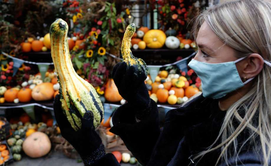 A woman compares two pumpkins at a Pumkin market in Covent Garden in London, Friday, Oct. 30, 2020. Pumpkin season has started with Halloween approaching on Saturday as trick or treating has been strongly discouraged due to the Coronavirus outbreak. Photo: Frank Augstein, AP / Copyright 2020 The Associated Press. All rights reserved