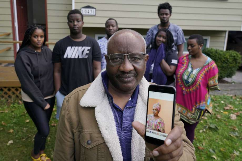 Sophonie Bizimana, center, a permanent U.S. resident who is a refugee from Congo, poses for a photo, Wednesday, Oct. 14, 2020, at his home in Kirkland, Wash., along with six of his children as he displays a cell-phone photo of his wife, Ziporah Nyirahimbya, who is in Uganda and has been unable so far to join him in the U.S. For decades, America admitted more refugees annually than all other countries combined, but that reputation has eroded during Donald Trump's presidency as he cut the number of refugees allowed in by more than 80 percent. Photo: Ted S. Warren, AP / Copyright 2020 The Associated Press. All rights reserved.