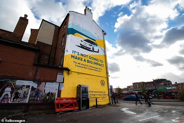 Pollution-eat adverts: Volkswagen has unveiled a new advertising campaign for its ID.3 electric car with painted murals using a material that is claimed to eliminate emissions. Pictured: One of the six ads in Birmingham