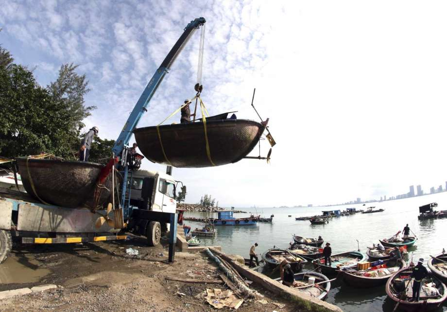 People move fishing boats to save place ahead of Typhoon Molave in Danang, Vietnam on Monday, Oct. 26, 2020. National agency forecasts the typhoon to hit Vietnam on Wednesday morning in the central region where 1.3 people could face evacuation. (Tran Le Lam/VNA via AP) Photo: Tran Le Lam, AP / VNA