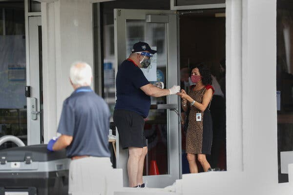 """An early voter receiving an """"I Voted"""" sticker at the St. Petersburg College polling site in Pinellas County, Fla., on Wednesday."""