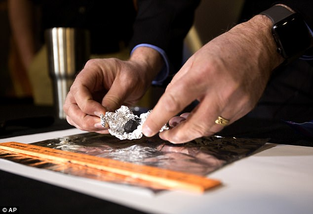 Astronomer Todd Slisher unfolds tin-foil to reveal a piece of the meteorite during the 2018 press conference