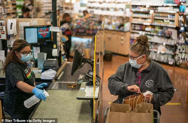 About 75% did not have any symptoms and workers who dealt with customers were five times more likely to test positive. Pictured: Cindy Lambing completes her shopping at Linden Hills Coop as cashier Sareena Tippett  sanitizes the check out space in Minnesota, May 2020