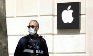 A municipal policeman wearing a protective face mask walks past the closed Apple store on the Champs-Elysees avenue in Paris in April 2020.