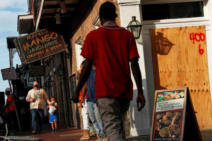 People walk by a closed bar in New Orleans. Democrats are not only striving to achieve a crisis recoverybut broader benefits for low-income and minority communities, a greener society, and a more highly skilled workforce