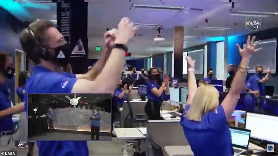 Mission complete! NASA scientists monitoring the mission raise their hands and celebrate after OSIRIS-REx collected the samples for several seconds and safely fired its thrusters to back away from the asteroid Tuesday evening