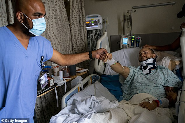 At least nine states set hospitalization records on Monday: Iowa, Kentucky, Minnesota, Montana, New Mexico, Ohio, South Dakota, West Virginia and Wisconsin. Pictured: Gordon Narayan gives a fist bump to Alex Sando at Harborview Medical Center in Seattle, Washington, August 20