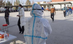A medical worker stands by as people line up to have their samples collected for nucleic acid testing in Shufu County of Kashgar Prefecture, northwest China's Xinjiang Uygur Autonomous Region, 26 October, 2020.