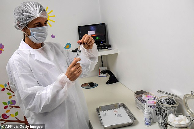 Reports say he was not part of the group that received the experimental jab and that he died from COVID-19 complications on October 15. Pictured:Brazilian pediatrician Dr Monica Levi, who received the COVID-19 vaccine, works at the Specialized Clinic in Infectious and Parasitic Diseases and Immunizations in Sao Paulo, Brazil, July 24