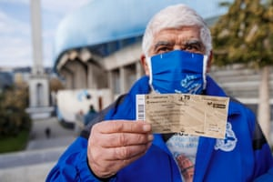 A fan proudly shows of his ticket for the game.