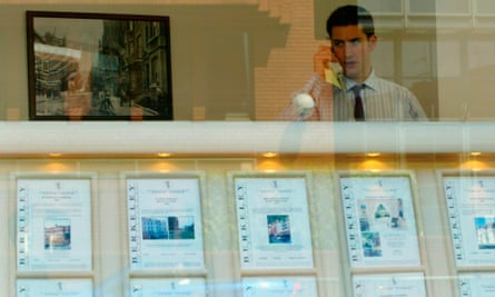 An estate agent talks on the phone behind a window display of properties for sale